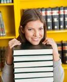 Kvinnlig student Resting Chin On Piled Books In Royaltyfria Bilder