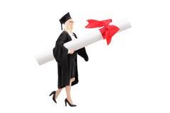 Kvinnlig student som bär ett enormt diplom Arkivbild
