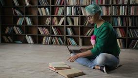 Kvinnlig student som direktanslutet e-lär med bärbara datorn arkivfilmer
