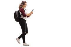 Kvinnlig student som går och ser mobiltelefonen royaltyfria foton