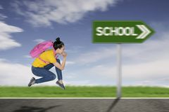 Kvinnlig student som kör in mot till skola royaltyfria foton