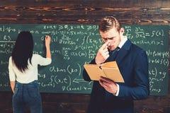 Kvinnlig student som löser likställande på brädet Ung lärare med det korta borstet som justerar exponeringsglas, medan läsa en bu arkivfoto