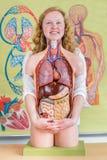 Kvinnlig student som omfamnar modellen av människokroppen med organ royaltyfri foto
