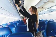 Kvinnlig student som sätter hennes handbagage in i det över huvudet skåpet på flygplanet royaltyfri bild