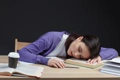 Kvinnlig student som sover med boken i klassrumskrivbord Arkivbilder