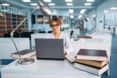 Kvinnlig student som studerar på bärbara datorn i arkiv royaltyfri bild