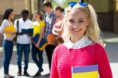 Kvinnlig student utomhus med hennes vänner royaltyfria bilder