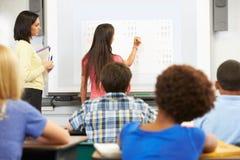 Kvinnlig student Writing Answer On Whiteboard royaltyfria bilder