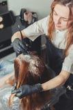 Kvinnlig stylist som applicerar en färg till klienthåret arkivfoton