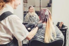 Kvinnlig stylist som applicerar en färg till klienthåret royaltyfri bild