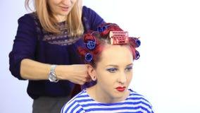 Kvinnlig stylist som skapar den perfekta frisyren med stor krullning f?r ung r?dh?rig mankvinna stock video