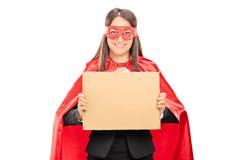 Kvinnlig superhero som rymmer ett tomt papptecken Arkivfoton