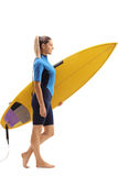 Kvinnlig surfare som går med surfingbrädan Fotografering för Bildbyråer
