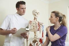 Kvinnlig tålmodig beskriva skuldraskada till osteopaten royaltyfria bilder
