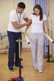 Kvinnlig tålmodig ha sjukgymnastik i sjukhus fotografering för bildbyråer