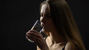Kvinnlig tagande minnestavla och dricksvatten, smärtstillande medel, sjukvård och medicin stock video