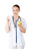 Kvinnlig tandläkare med det gröna äpplet och den stora tanden royaltyfri fotografi