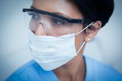 Kvinnlig tandläkare som bär den kirurgiska maskeringen och säkerhetsexponeringsglas Royaltyfria Bilder