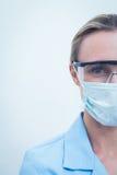 Kvinnlig tandläkare som bär den kirurgiska maskeringen och säkerhetsexponeringsglas Fotografering för Bildbyråer