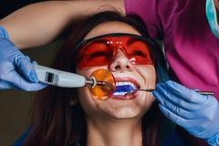 Kvinnlig tandläkare som behandlar en patient En ung kvinna som sitter i tandläkarens stol royaltyfria bilder