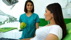 Kvinnlig tandläkare som erbjuder det tålmodiga saftiga äpplet, vård- rekommendationer för specialister arkivfoton
