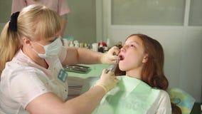 Kvinnlig tandläkare som gör den bedövande injektionen till hennes tålmodiga flicka i tand- kabinett stock video