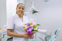 Kvinnlig tandläkare som ler, med en bukett av blommor, i tand- kontor Nationell dag för tandläkare` s royaltyfri fotografi