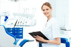 Kvinnlig tandläkare som poserar mot en bakgrund av tand- utrustning i en tand- klinik Hon rymmer minnestavlan för legitimationsha Royaltyfri Bild