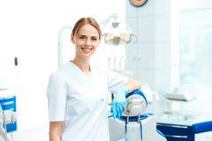 Kvinnlig tandläkare som poserar mot en bakgrund av tand- utrustning i en tand- klinik Hon sätter på handskar Royaltyfria Bilder