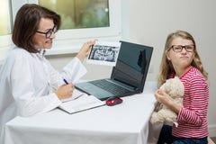 Kvinnlig tandläkareorthodontist med röntgenstrålen som talar till ett barn Royaltyfria Bilder