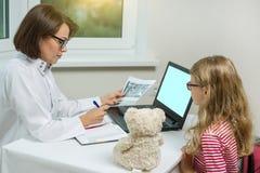 Kvinnlig tandläkareorthodontist med röntgenstrålen som talar till ett barn Fotografering för Bildbyråer