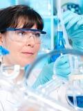 Kvinnlig tech fungerar i kemiskt labb Arkivbild
