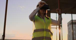 Kvinnlig tekniker i hardhat med VR-exponeringsglas som planlägger konstruktionsprojekt på produktionsanläggningen lager videofilmer