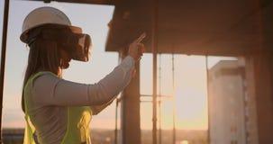 Kvinnlig tekniker i hardhat med VR-exponeringsglas som planlägger konstruktionsprojekt på produktionsanläggningen arkivfilmer
