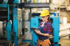 Kvinnlig tekniker Inspecting Machine Royaltyfria Bilder