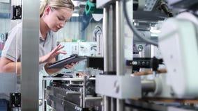 Kvinnlig tekniker med den digitala minnestavlan som kontrollerar den automatiserade maskinen i fabrik arkivfilmer