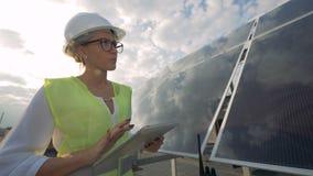 Kvinnlig tekniker som kontrollerar solbatterier på ett tak Modernt innovativt branschbegrepp arkivfilmer