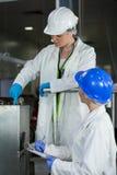 Kvinnlig teknikerhandstil på notepaden, medan undersöka kött som bearbetar maskinen fotografering för bildbyråer