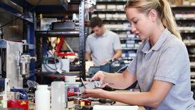 Kvinnlig teknikerIn Factory Measuring del på arbetsbänken genom att använda mikrometer arkivfilmer