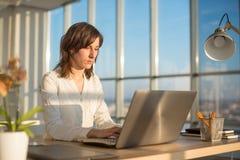Kvinnlig teleworker som smsar genom att använda bärbara datorn och internet som direktanslutet arbetar Freelancer som skriver det Royaltyfri Bild