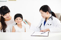 Kvinnlig temperatur för doktor Taking genom att använda i öratermometer Arkivbilder
