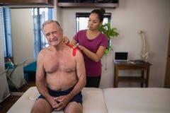 Kvinnlig terapeut som applicerar det elastiska terapeutiska bandet på skuldra av att rynka pannan den passande shirtless höga man arkivfoton