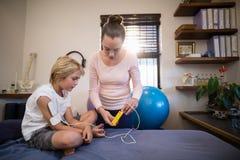 Kvinnlig terapeut som visar den elektriska muskelstimulansmaskinen till pojkesammanträde på säng royaltyfria foton