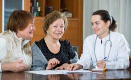 Kvinnlig therapeutist som konsulterar höga patienter i klinik Arkivfoto