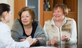 Kvinnlig therapeutist som konsulterar höga patienter i klinik Arkivfoton