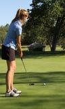 Kvinnlig tonårig golfare som sätter på gräsplan Arkivfoto