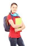 Kvinnlig tonåring med skolväskan och hörlurar som rymmer anteckningsböcker Arkivbild