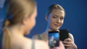 Kvinnlig ton?ring som tar selfieframdelen av spegeln vid smartphonen, sk?nhetblogger lager videofilmer