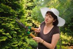 Kvinnlig trädgårdsmästare i den vita hatten Arkivbild