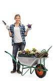 Kvinnlig trädgårdsmästareinnehavblomma och spade Arkivbild